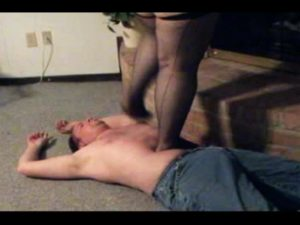 woman in nylons trampling a mans stomach by a fireplace